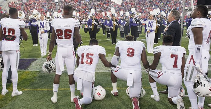 Nebraska linebacker Michael Rose-Ivey (15), defensive end DaiShon Neal (9) and linebacker Mohamed Barry (7) kneel during the national anthem before the team's NCAA college football game against Northwestern in Evanston, Ill., on Saturday, Sept. 24, 2016. Rose-Ivey said Monday he and his family have received racially charged criticism on social media, and said the responses show why the protest is necessary. (Matt Ryerson/Journal Star via AP)