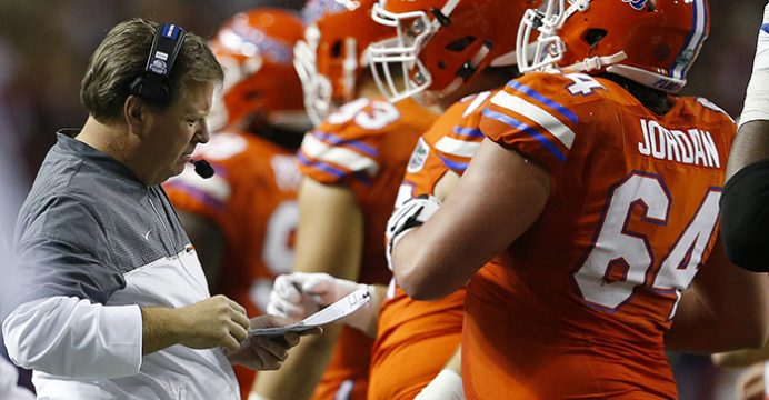Florida head coach Jim McElwain looks over plays during the first half of the Southeastern Conference championship NCAA college football game between Alabama and Florida, Saturday, Dec. 3, 2016, in Atlanta.(AP Photo/Butch Dill)