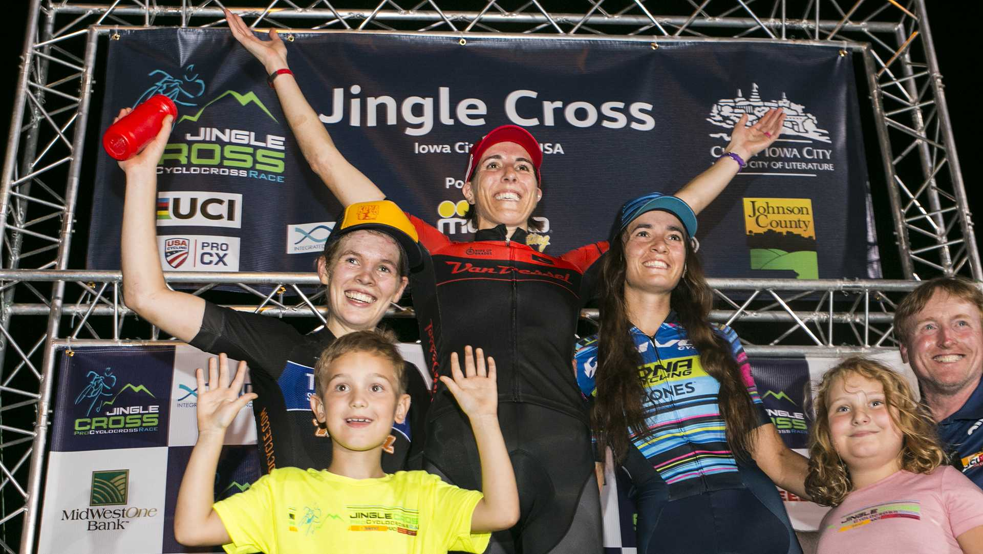 Team S&M CX's Clara Honsigner, left, Van Dessel Factory Team's Sunny Gilbert, center, and Sofia Gomez Villafane, right, stand on the podium after a cyclocross race at Jinglecross at the Johnson County fairgrounds on Saturday, Sept. 16, 2017. After both of the C2 races podium finishers had a symbolic wave to children in the Stead Family Children's Hospital. Saturday night featured C2 men's and women's UCI races, Sept. 17 will host the UCI Telenet World Cup. (Joseph Cress/The Daily Iowan)