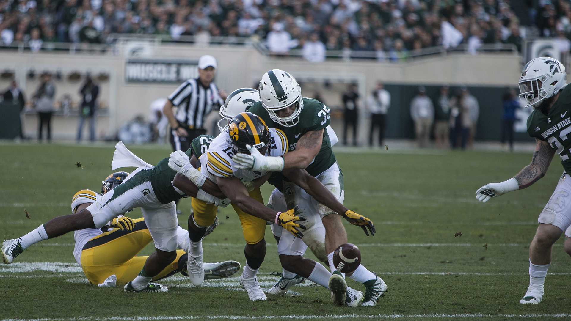 Iowa wide receiver Brandon Smith (12) attempts to recover a fumble forced by Michigan State's Joe Bachie during the game between Iowa and Michigan State at Spartan Stadium on Saturday, Sept. 30, 2017. The Hawkeyes fell to the Spartans with a final score of 10-17. (Ben Smith/The Daily Iowan)