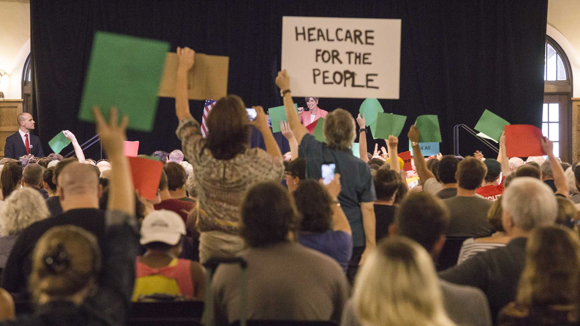 Participants display their signs in protest to Senator Joni Ernst's policy proposal at a Town Hall meeting in the Iowa Memorial Union on Friday, Sept. 22, 2017. (James Year/The Daily Iowan)