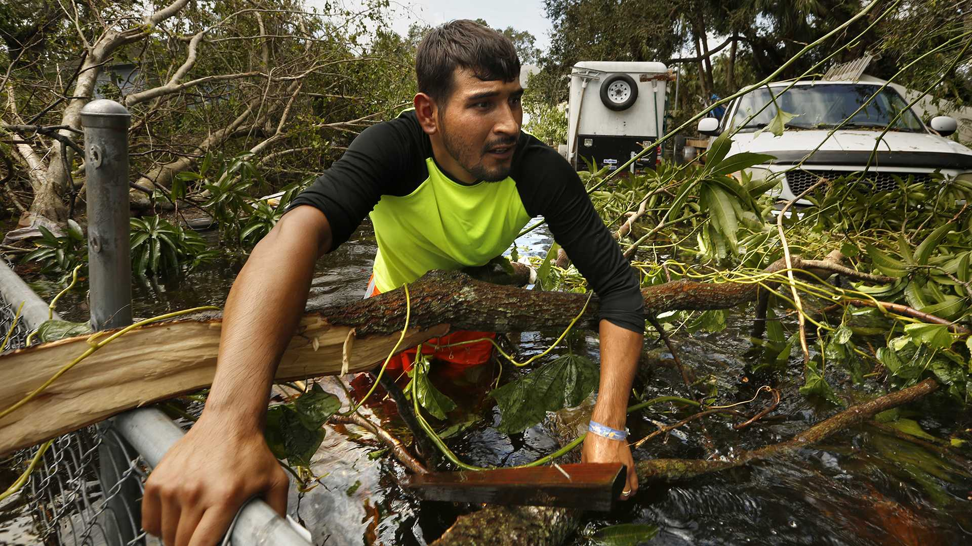 Israel Alvarado, 25, tries to open the yard fence blocked by fallen tree branches so that he can retrieve a generator from the property. In Bonita Springs, Fla., floodwaters reached waist deep in some areas, flooding homes and cars. Some residents returned on Monday, Sept. 11, 2017 to retrieve belongings. (Carolyn Cole/Los Angeles Times/TNS)