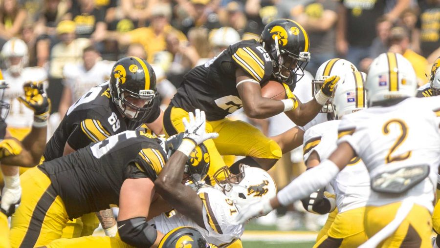 Iowa+running+back+Akrum+Wadley+dives+over+the+Wyoming+defense+during+the+season+opener+against+Wyoming+on+Saturday%2C+Sep.+2%2C+2017.+The+Hawkeyes+went+on+to+defeat+the+Cowboys%2C+24-3.+%28Ben+Smith%2FThe+Daily+Iowan%29