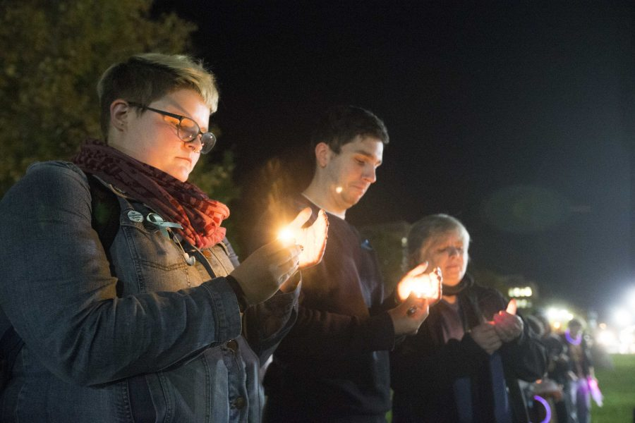 From+left%3A+UI+senior+Ellen+Kuehnle+and+Women%27s+Resource+and+Action+Center+employees+Cody+Howell+and+Laurie+Haag+hold+candles+during+the+UI+Sister+Vigil+for+Survivors+of+Campus+Sexual+Assault+on+the+Pentacrest+on+Tuesday%2C+Oct.+17%2C+2017.+The+event+included+letter+writing+to+Iowa+senators+and+the+signing+of+thank+you+state+of+Iowa+flags+to+senators+fighting+the+withdrawal+of+Title+IX+protections+for+survivors+of+sexual+assault.+%28Lily+Smith%2FThe+Daily+Iowan%29