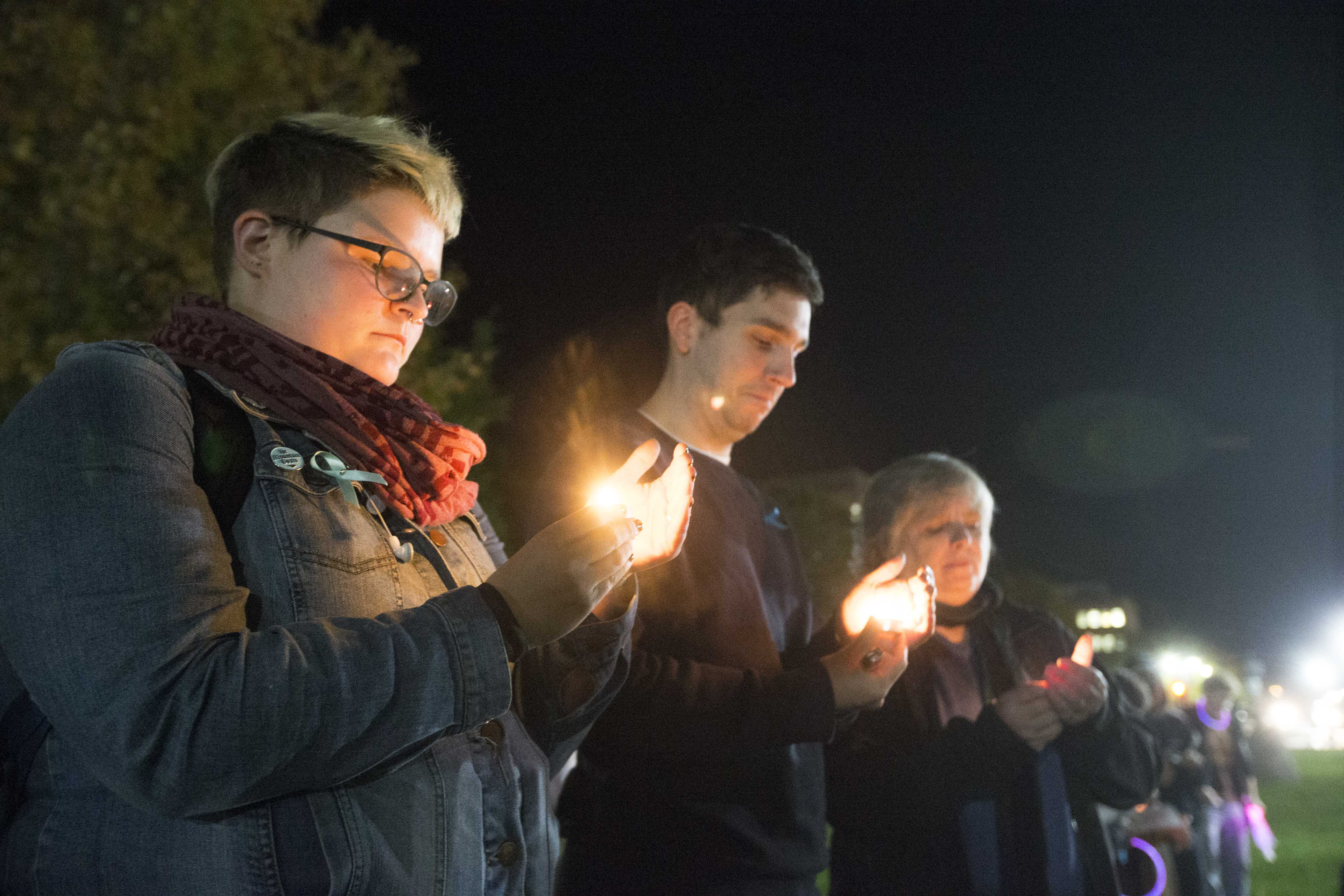 From left: UI senior Ellen Kuehnle and Women's Resource and Action Center employees Cody Howell and Laurie Haag hold candles during the UI Sister Vigil for Survivors of Campus Sexual Assault on the Pentacrest on Tuesday, Oct. 17, 2017. The event included letter writing to Iowa senators and the signing of thank you state of Iowa flags to senators fighting the withdrawal of Title IX protections for survivors of sexual assault. (Lily Smith/The Daily Iowan)