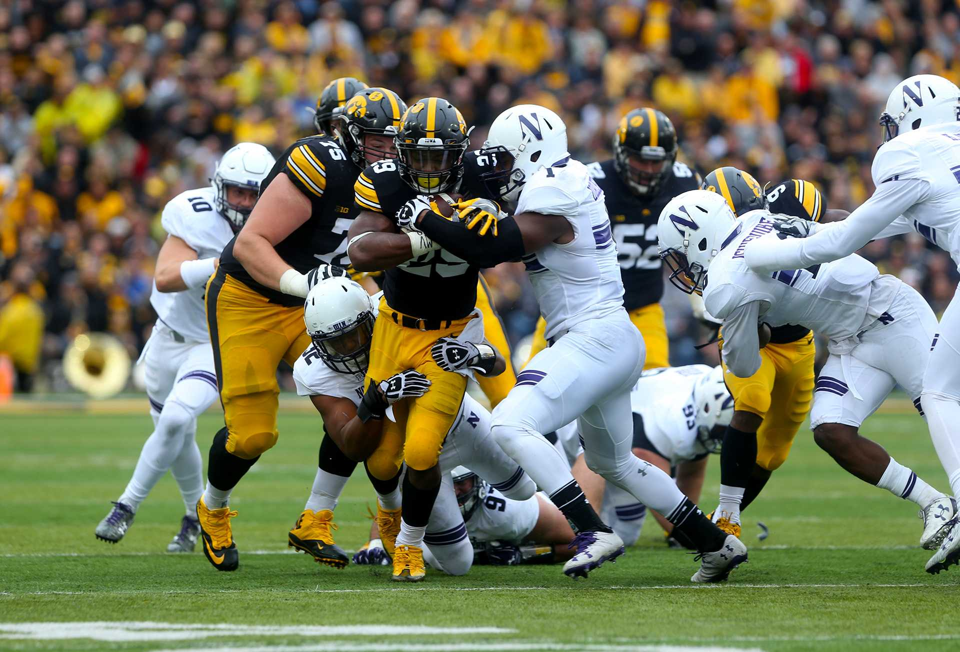 FILE - Northwestern linebacker Nate Hall tackles Iowa running back LeShun Daniels during the game between Iowa and Northwestern in Iowa City on Saturday, October 1, 2016. The Wildcats defeated the Hawkeyes 38-31. (The Daily Iowan/file)