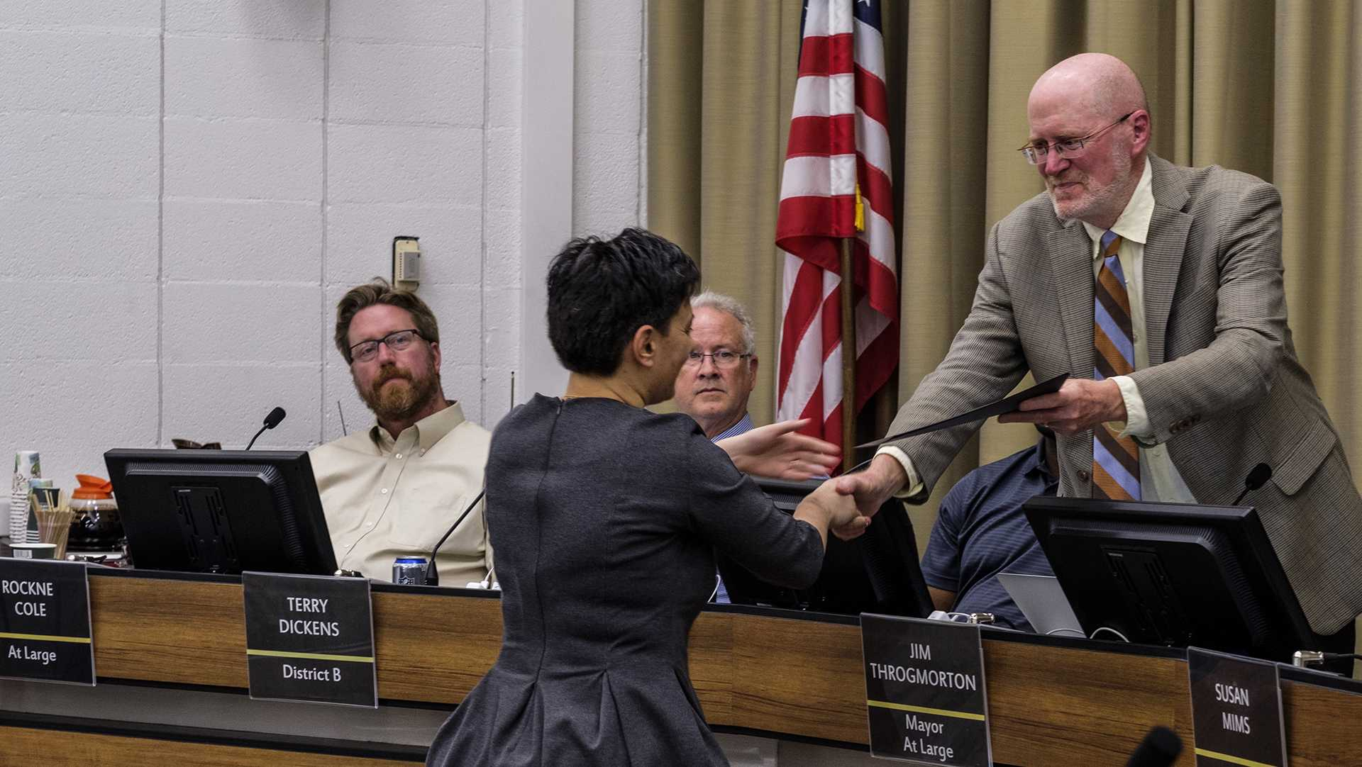 Maria Padron accepts a proclamation on the observance of United Nations Day during a city council meeting on Tuesday, Oct. 17, 2017. (Nick Rohlman/The Daily Iowan)