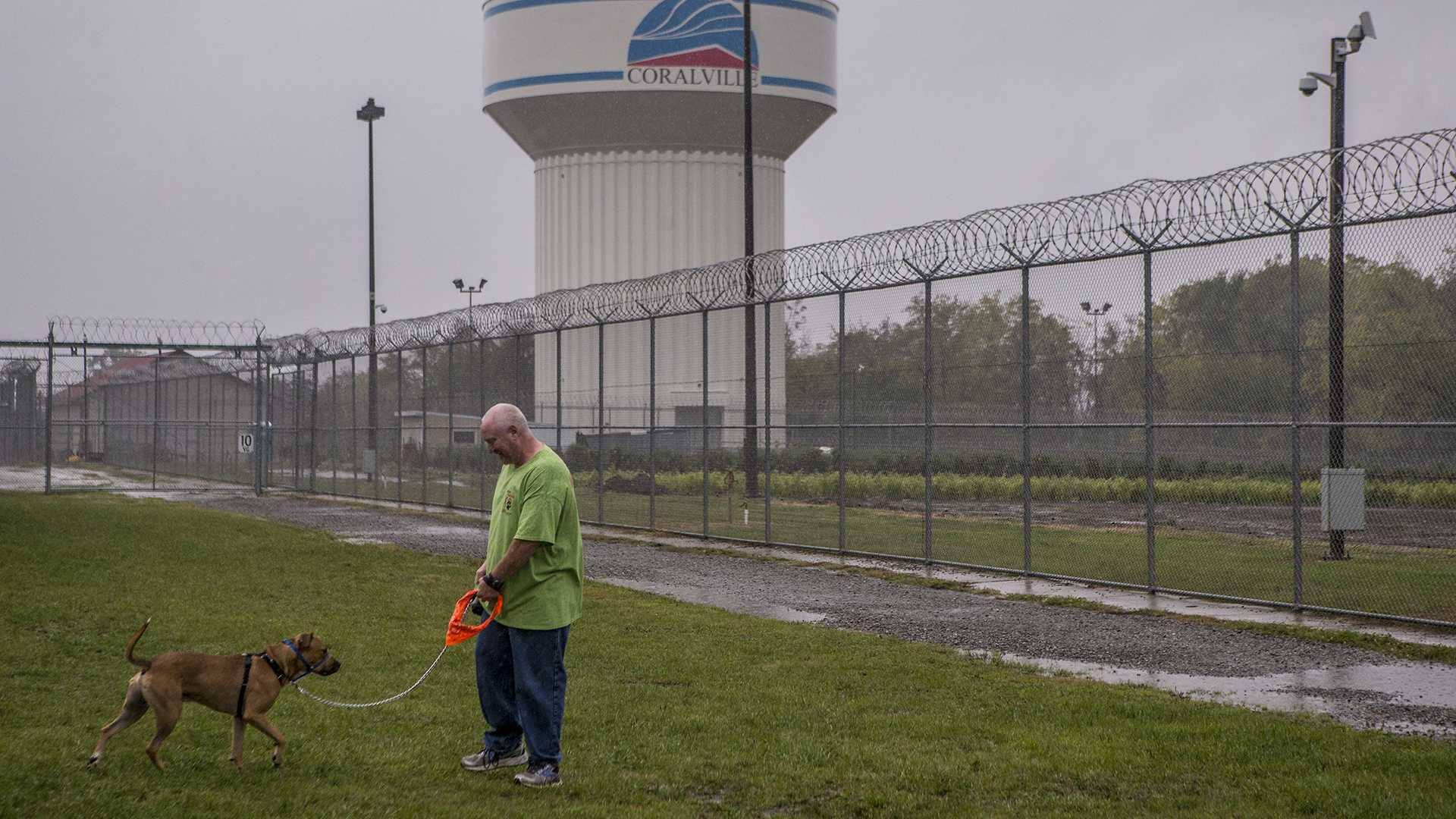 Terry, an inmate volunteer, on Tuesday walks Russ, a shelter dog who was placed at the Iowa Medical & Classification Center as part of a program in which inmates teach shelter dogs obedience and help to rehabilitate them for adoption or placement. (Nick Rohlman/The Daily Iowan)