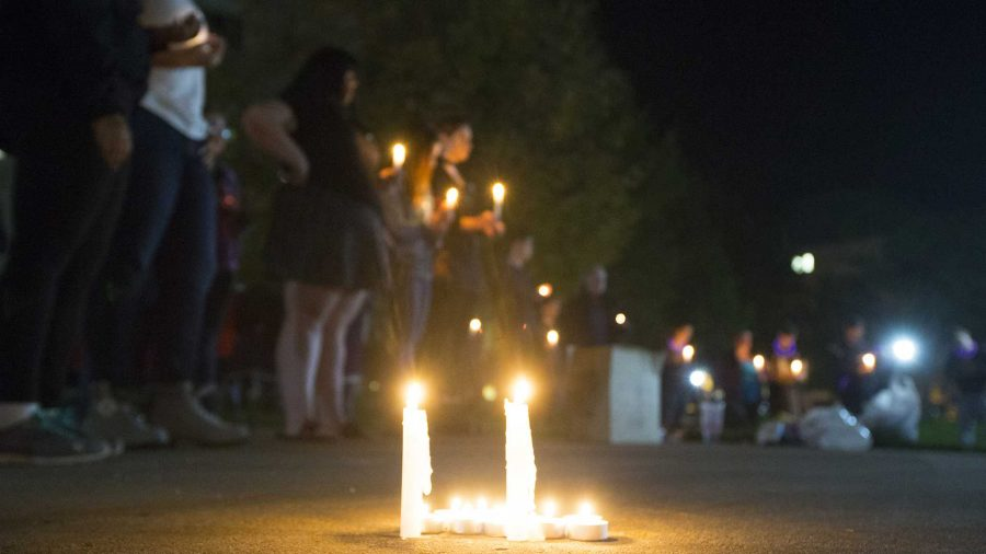 Candles+burn+during+the+UI+Sister+Vigil+for+Survivors+of+Campus+Sexual+Assault+on+the+Pentacrest+on+Tuesday%2C+Oct.+17%2C+2017.+The+event+included+letter+writing+to+Iowa+senators+and+the+signing+of+thank+you+state+of+Iowa+flags+to+senators+fighting+the+withdrawal+of+Title+IX+protections+for+survivors+of+sexual+assault.+%28Lily+Smith%2FThe+Daily+Iowan%29