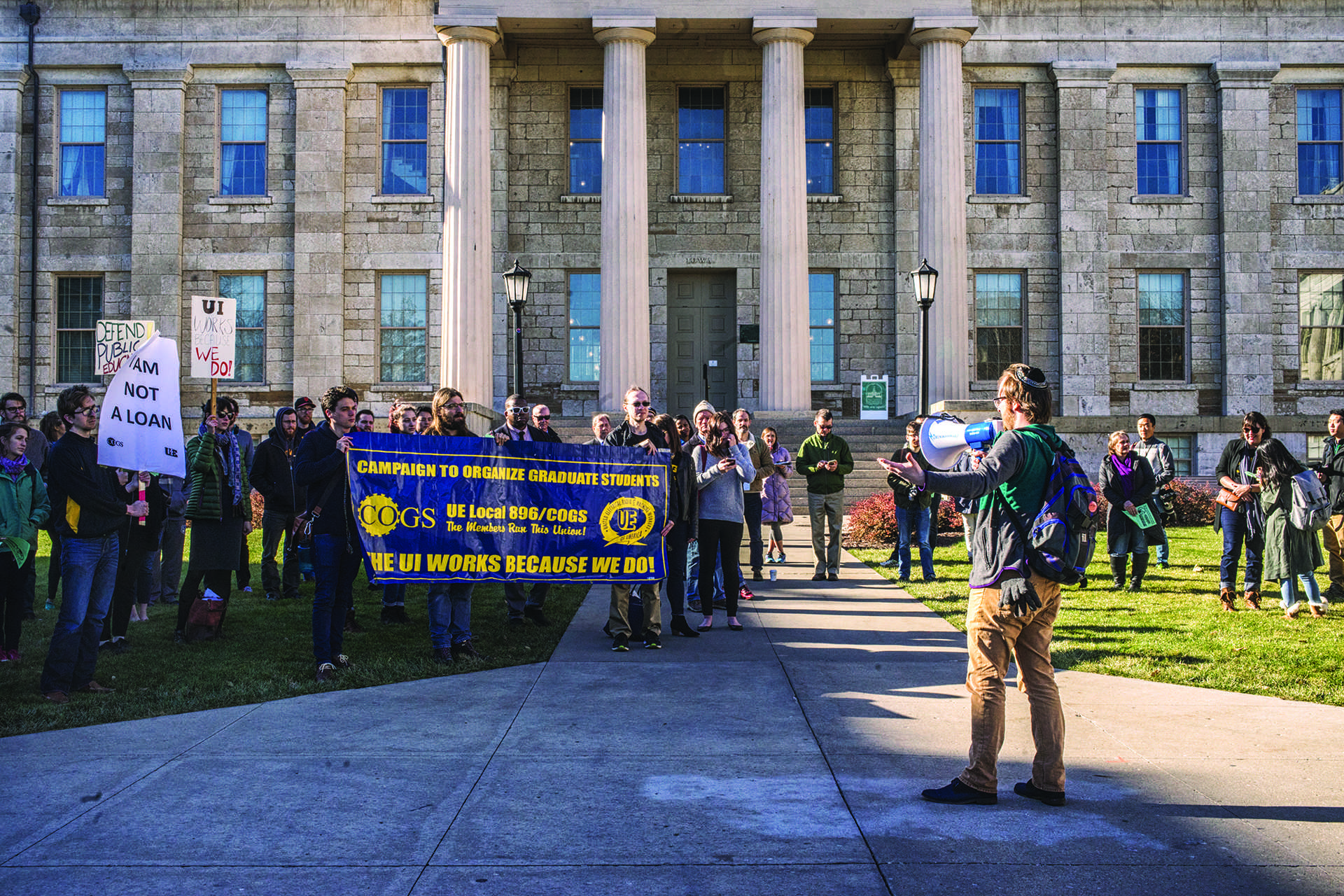 COGS financial officer Landon Elkind speaks to the crowd at a protest on the Pentacrest on Wednesday, Nov. 29, 2017. The students protested a current GOP tax proposal that would repeal tax exemption on students' tuition waivers, making that income taxable. That provision in the House version of this legislation has been concerning for graduate students. (James Year/The Daily Iowan)
