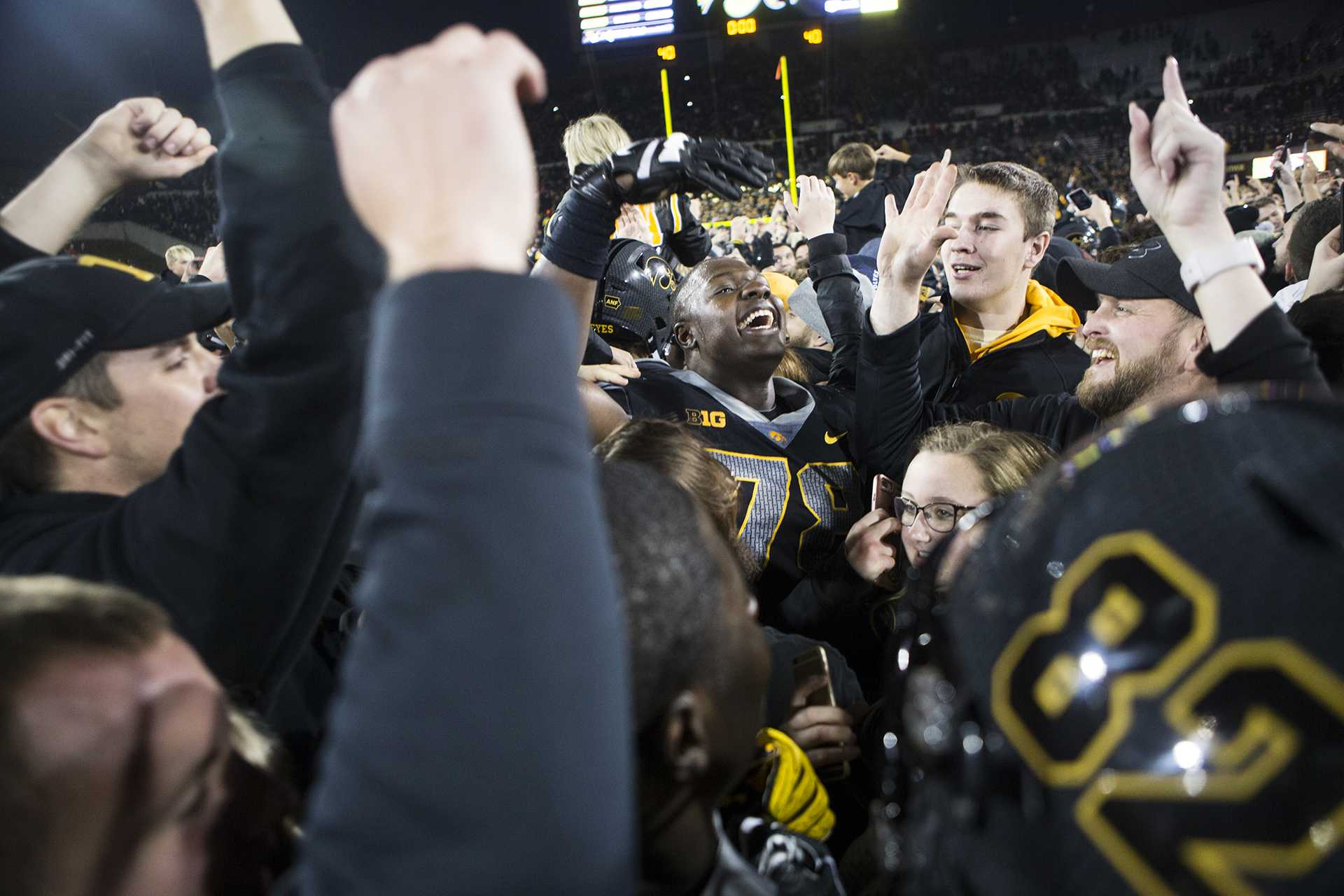 Fans celebrate with Iowa offensive linemen James Daniels while storming the field during the Iowa/Ohio State football game in Kinnick Stadium on Saturday, Nov. 4, 2017. The Hawkeyes defeated the Buckeyes in a storming fashion, 55-24. (Joseph Cress/The Daily Iowan)