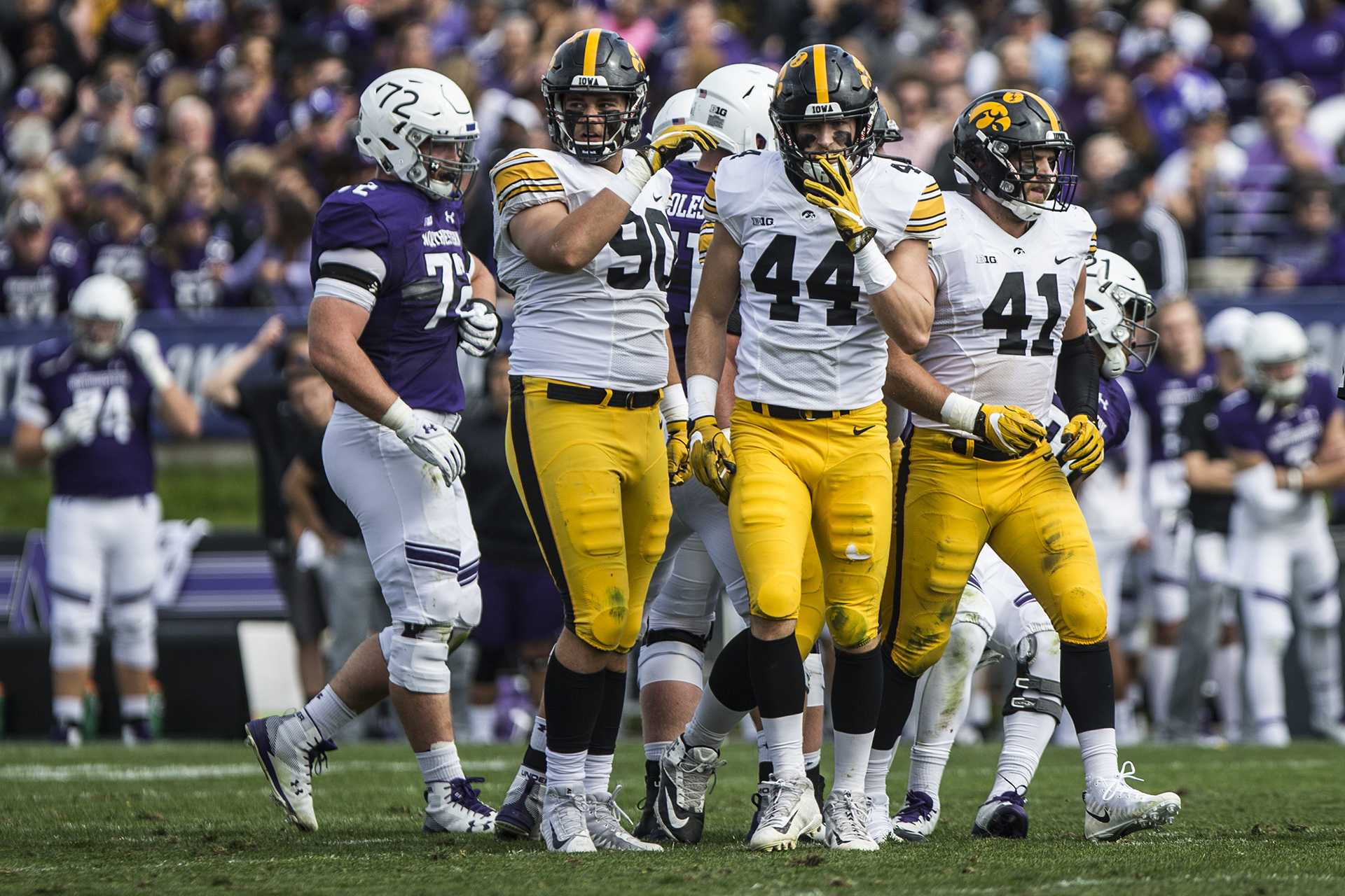 Iowa's Sam Brincks (90), Ben Niemann (44), and Bo Bower (41) walk off the field during the game between Iowa and Northwestern at Ryan Field in Evanston, Ill. on Saturday, Oct. 21, 2017. The Wildcats defeated the Hawkeyes 17-10 in overtime. (Ben Smith/The Daily Iowan)