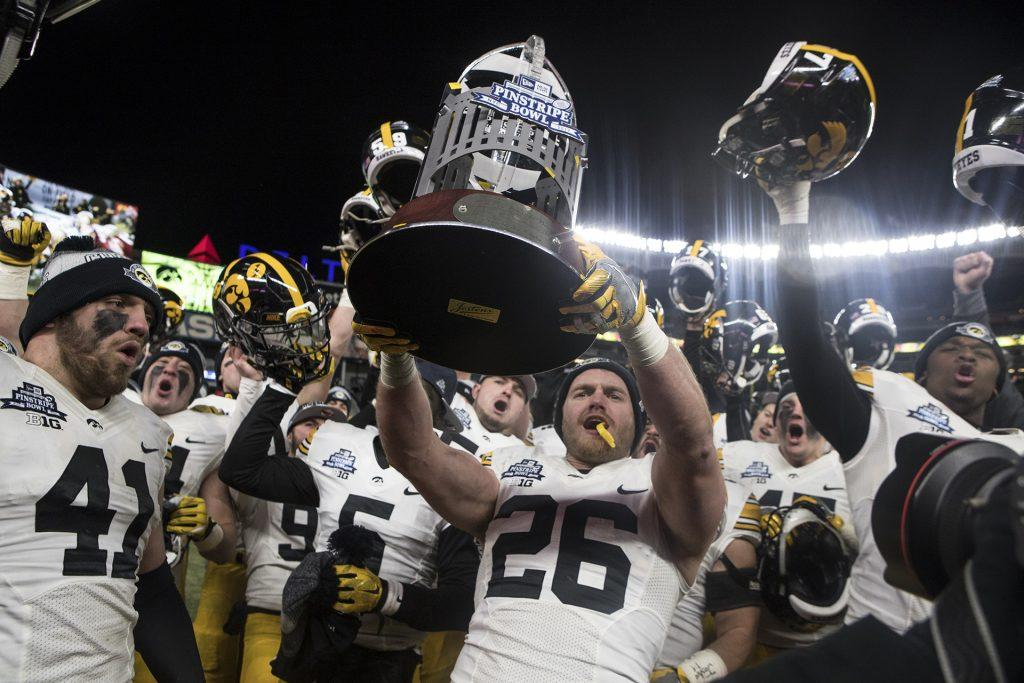 Iowa%27s+Kevin+Ward+%2826%29+holds+up+the+New+Era+Pinstripe+Bowl+trophy+after+the+Hawkeyes+beat+Boston+College+in+the+Pinstripe+Bowl+at+Yankee+Stadium+in+New+York+on+Wednesday%2C+Dec.+27.+The+Hawkeyes+went+on+to+win+27-20.+%28Ben+Allan+Smith%2FThe+Daily+Iowan%29
