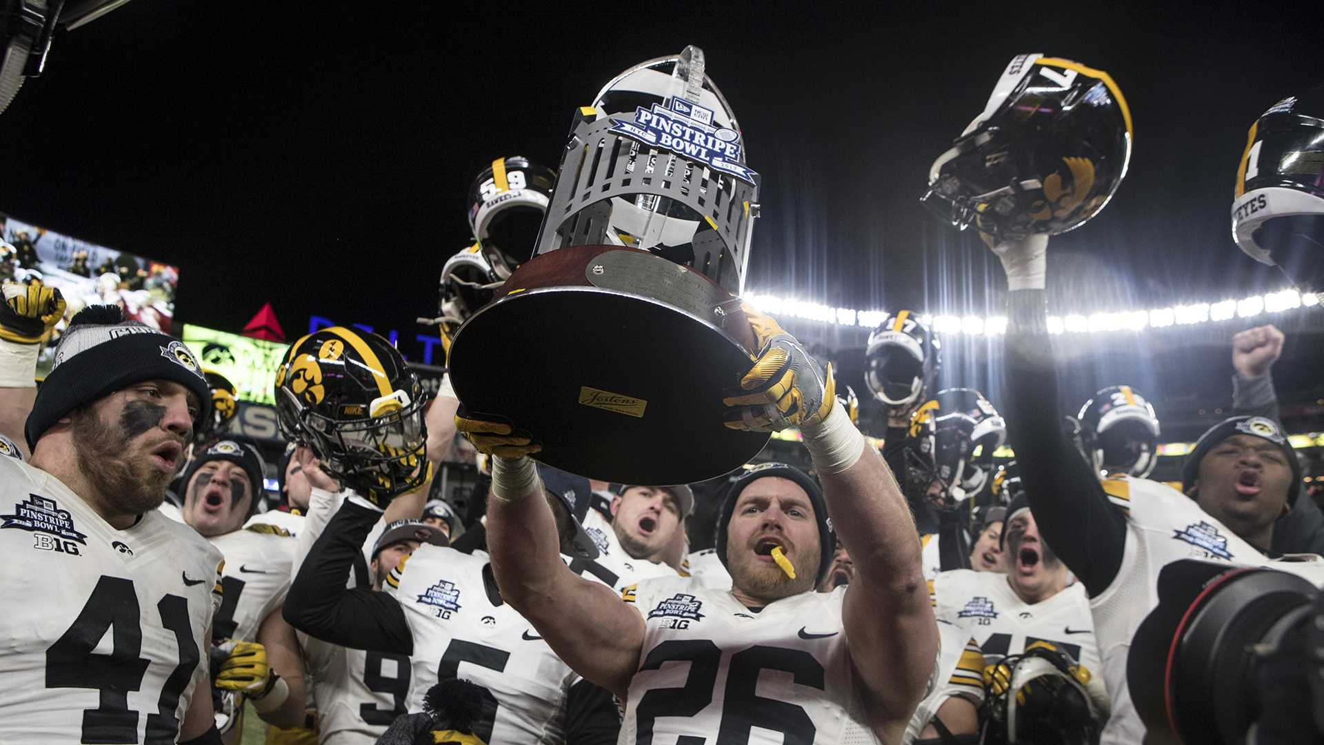 Iowa's Kevin Ward (26) holds up the New Era Pinstripe Bowl trophy after the Hawkeyes beat Boston College in the Pinstripe Bowl at Yankee Stadium in New York on Wednesday, Dec. 27. The Hawkeyes went on to win 27-20. (Ben Allan Smith/The Daily Iowan)