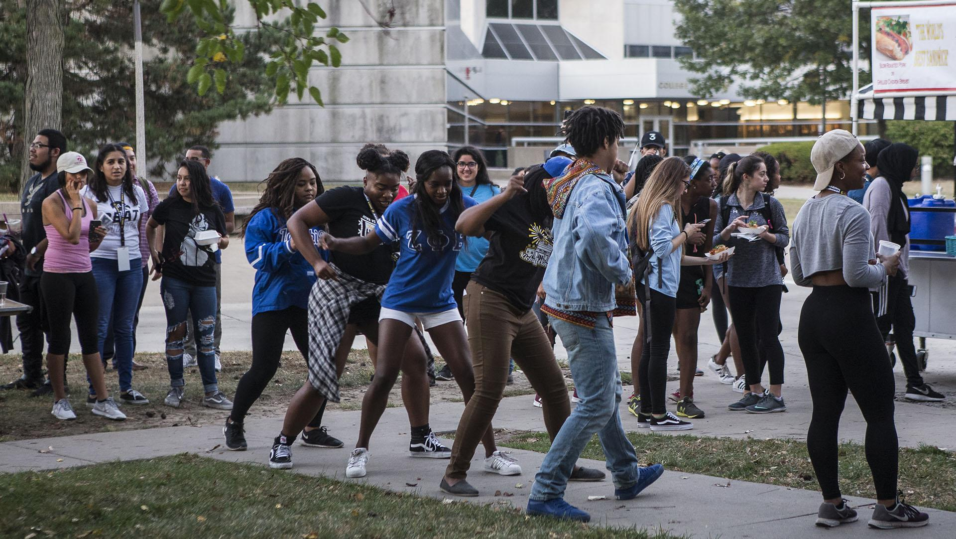 Members of the National Pan-Hellenic Council perform a dance at the African-American Cultural House on Monday, Oct. 2, 2017. Members of the community could attend the event for free as a part of the University's Homecoming Week. (Ben Smith/The Daily Iowan)