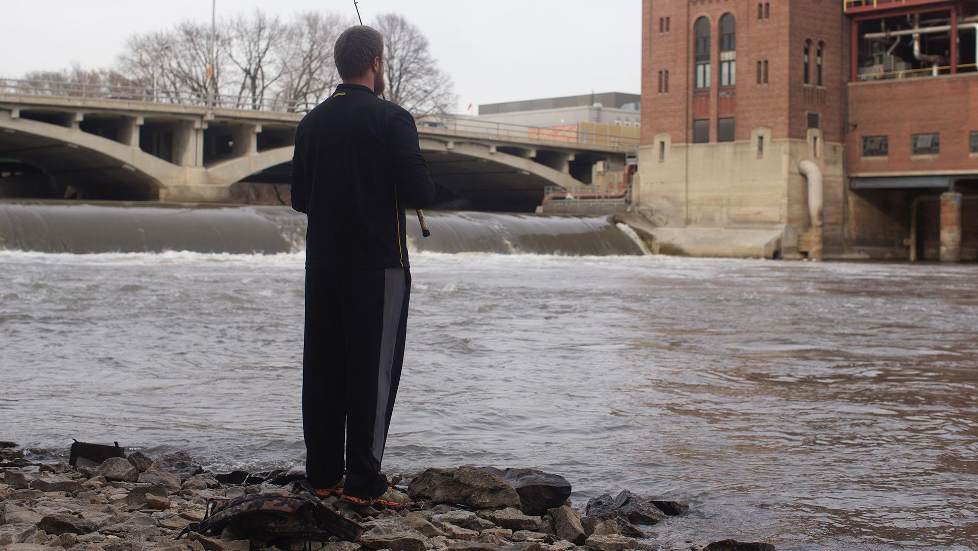 Andy DeCamp a freshman at The University of Iowa fishes at the base of the Iowa River dam on, Tuesday March 22, 2016. The first day of the spring season was Sunday March 20, the day before students returned from spring break. (The Daily Iowan/Jordan Gale)