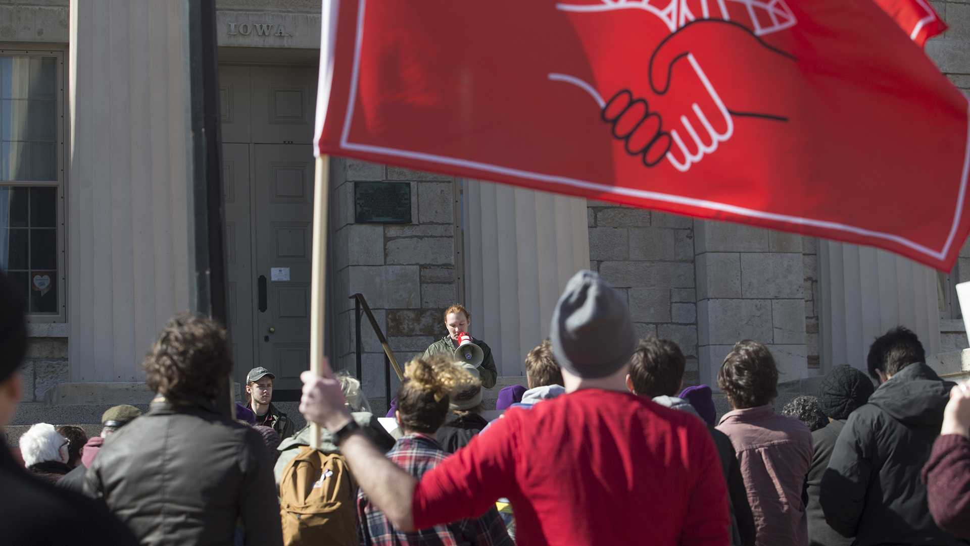 Bill Harshbarger hoists a Democratic Socialists of America  flag as undergraduate students speak to show solidarity during a COGS protest on the Pentacrest Feb. 26, 2018. COGS, or Campaign to Organize Graduate Students, led a rally to raise awareness for the Supreme Court Janus case, which will negatively impact the ability to form unions and wages amongst public workers. (Katie Goodale /The Daily Iowan)
