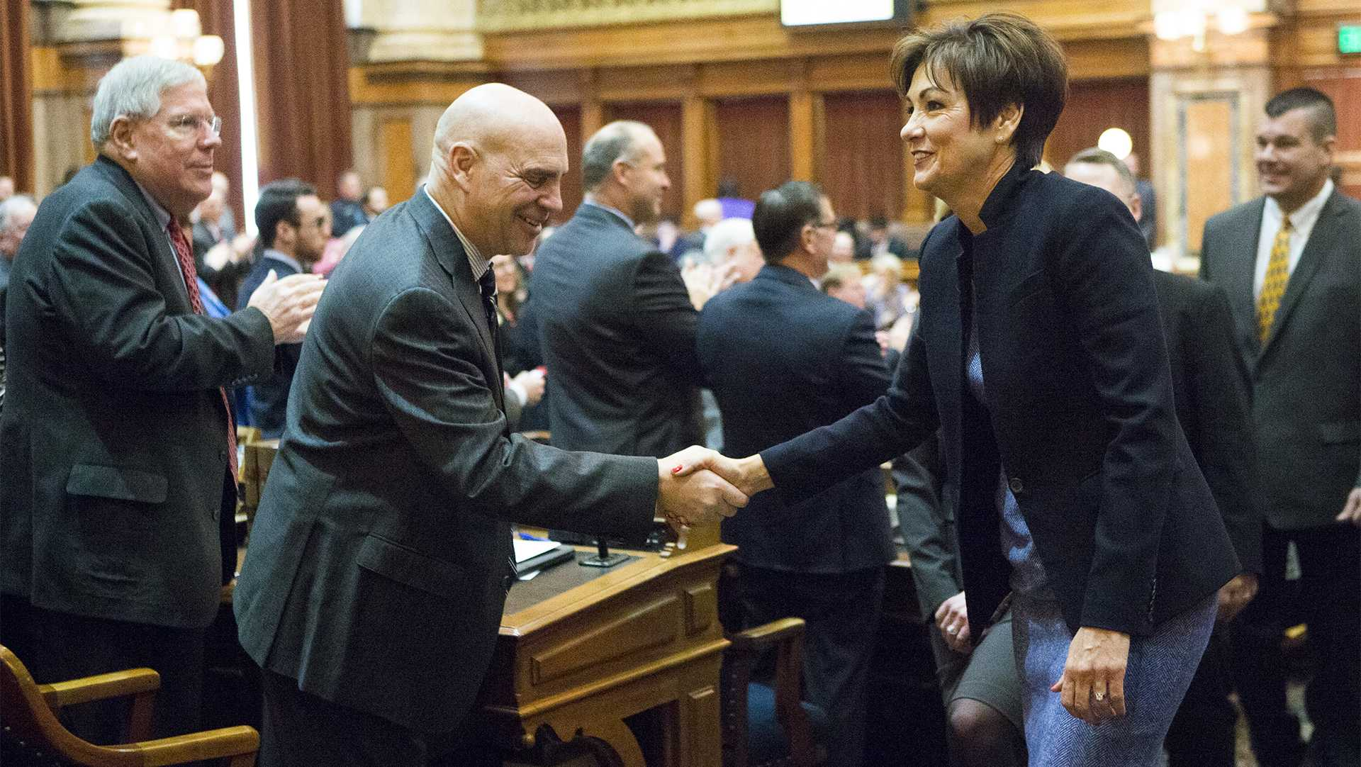 Iowa Gov. Kim Reynolds shakes hands with after Rep. Dave Jacoby, D-Coralville, while Sen. Robert E. Dvorsky, D-Coralville, claps after her first Condition of the State address in the Iowa State Capitol in Des Moines on Tuesday, Jan. 9, 2018. Reynolds took over the governor office in May of 2017. (Joseph Cress/The Daily Iowan)