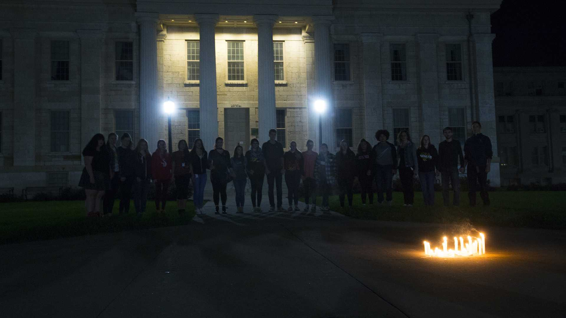 Survivors and allies hold hands during the UI Sister Vigil for Survivors of Campus Sexual Assault on the Pentacrest on Tuesday, Oct. 17, 2017. The event included letter writing to Iowa senators and the signing of thank you state of Iowa flags to senators fighting the withdrawal of Title IX protections for survivors of sexual assault. (Lily Smith/The Daily Iowan)