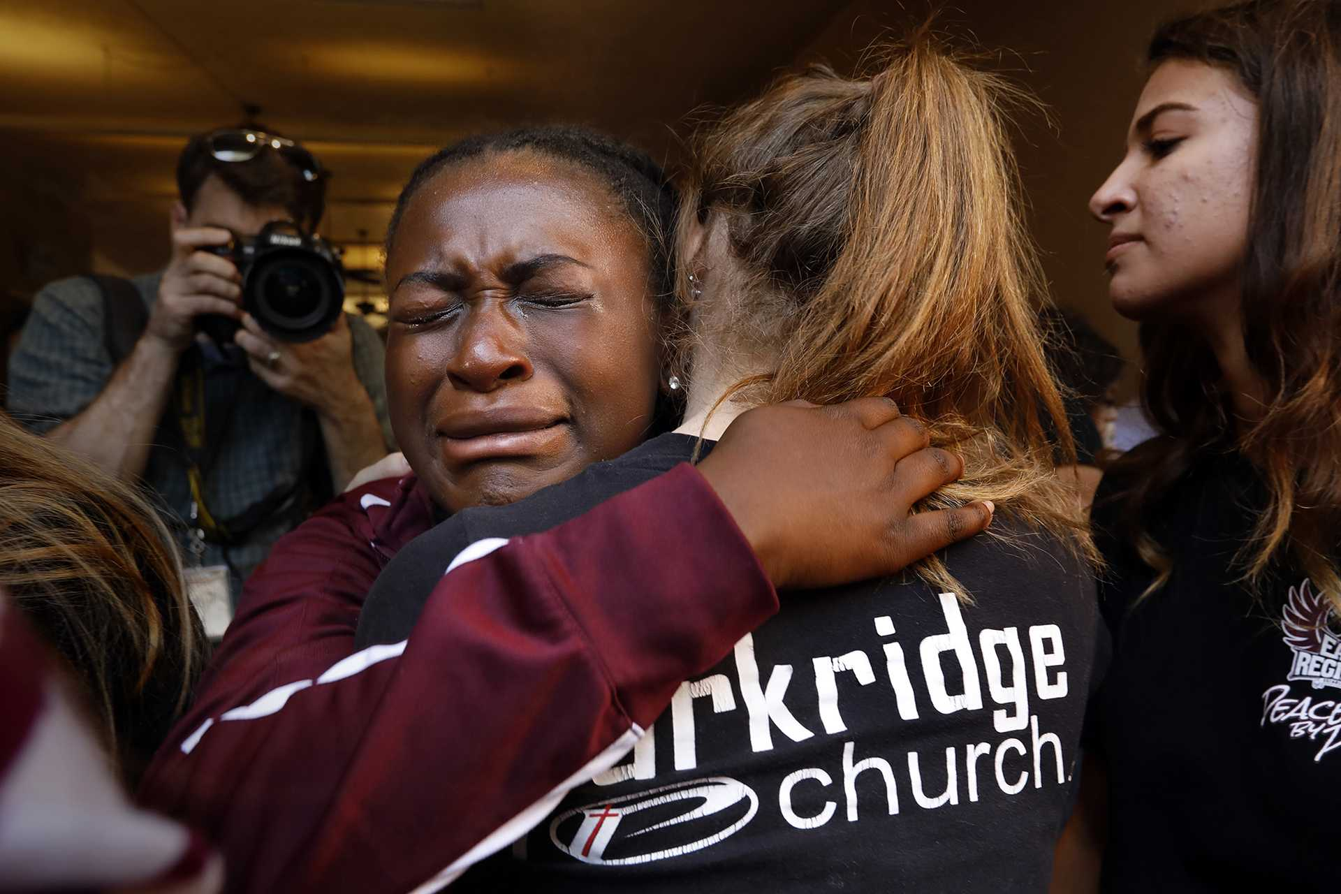 Marla Eveillard, 14, grieves with friends before the start of the community prayer vigil on Thursday, Feb. 15, 2018, one day after the deadly shooting at Marjory Stoneman Douglas High School in Parkland, Fla. that left 17 dead and 14 injured. (Carolyn Cole/Los Angeles Times/TNS)