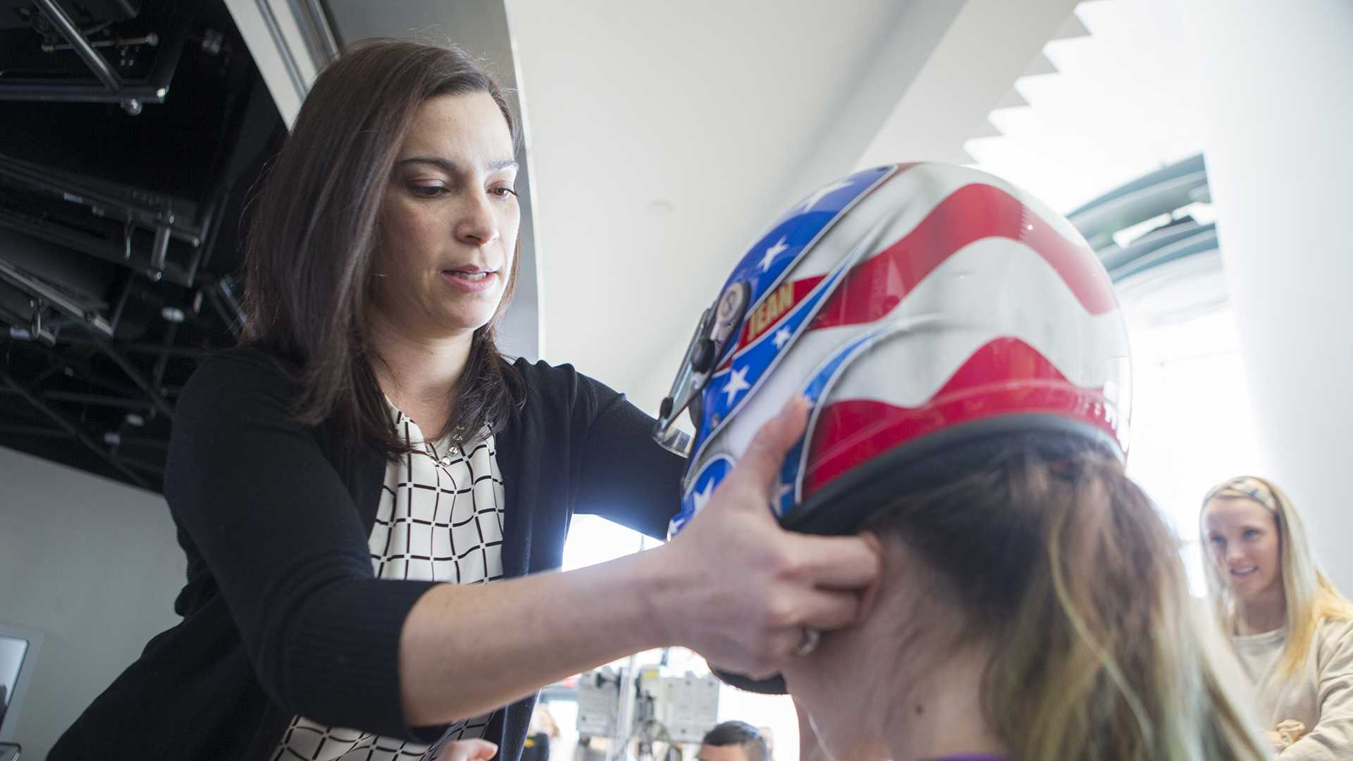 U.S. Olympian Jean Prahm helps a Stead Family Children's Hospital patient try on her bobsled helmet during Prahm's visit to the Stead Family Children's Hospital on Tuesday, Feb. 13, 2018. Prahm was on the U.S. Olympic women's bobsled team from 1996-2006. (Lily Smith/The Daily Iowan)