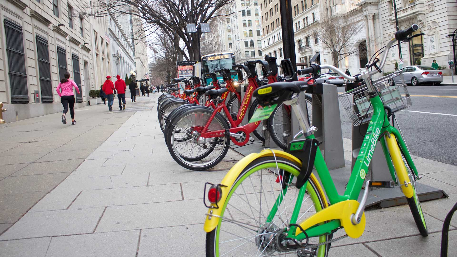 A dockless bike stands before a row of docked bikes in Washington on March 12. Iowa City is considering bringing a dockless bike-share system to town after the technology has had success in many cities nationwide. (Katelyn Weisbrod/The Daily Iowan)