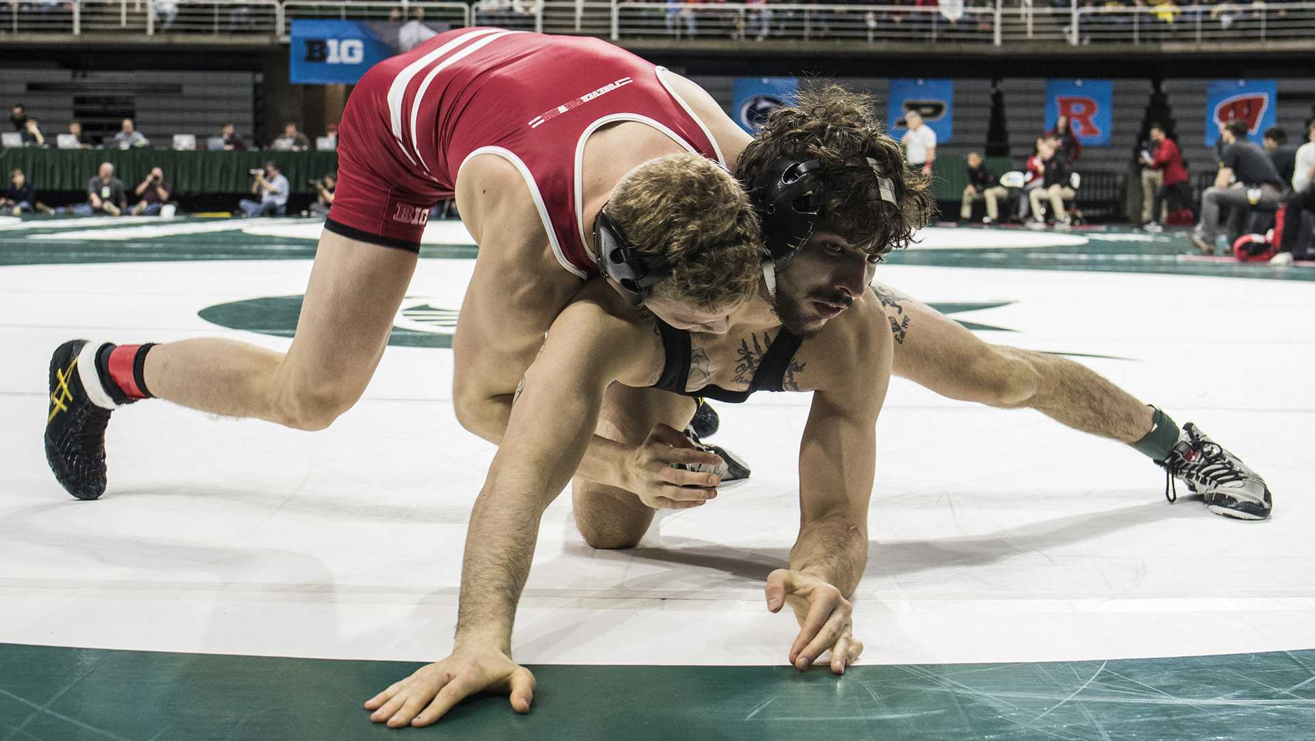 Wisconsin's 141-pound Eli Stickley, left, scores two on Iowa's Vince Turk during Big Ten Wrestling Championships Day 1 at the Breslin Student Events Center in East Lansing, MI on Saturday, Mar. 3, 2018. (Ben Allan Smith/The Daily Iowan)