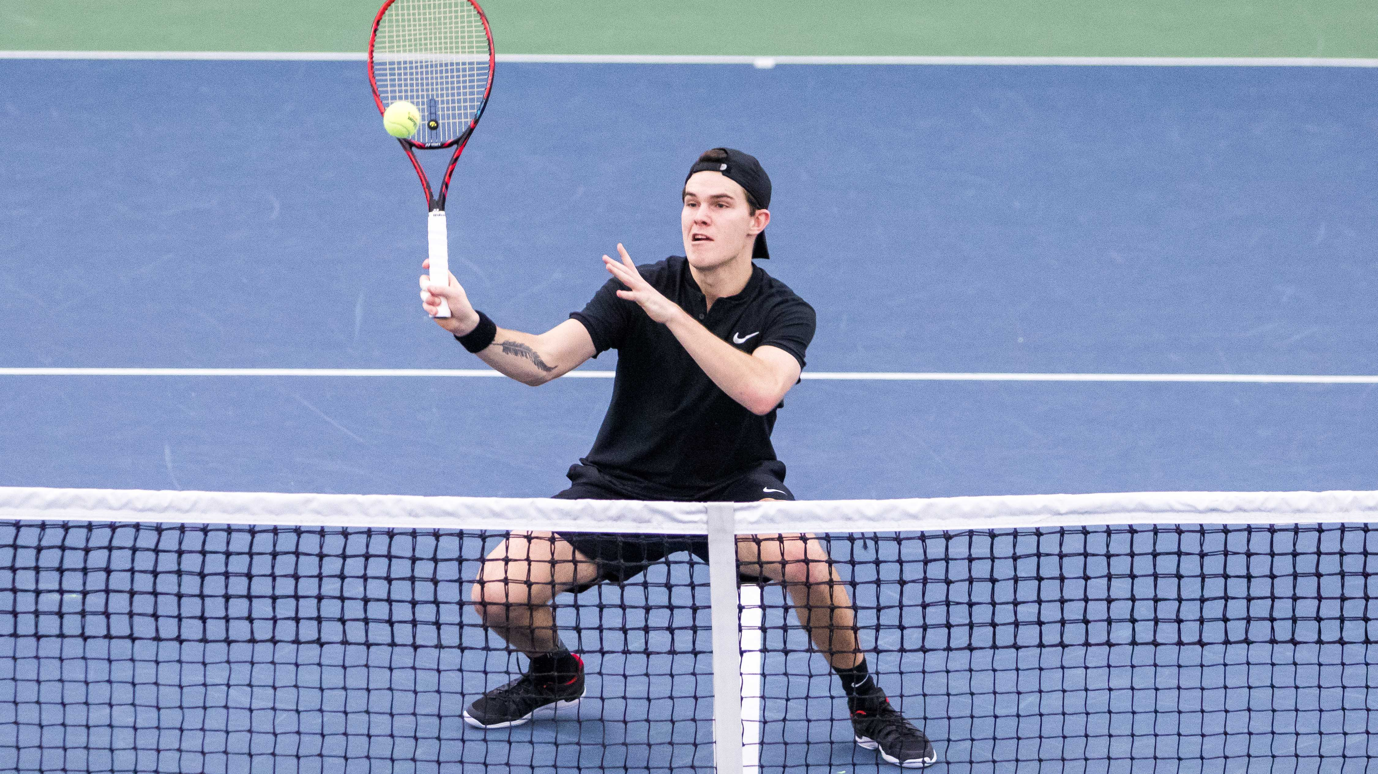 Iowa tennis player Jonas Larson  plays at the net during a doubles match against Cornell University on Friday, Mar. 2, 2018. The Big Red defeated the Hawkeyes 4-3. (David Harmantas/The Daily Iowan)