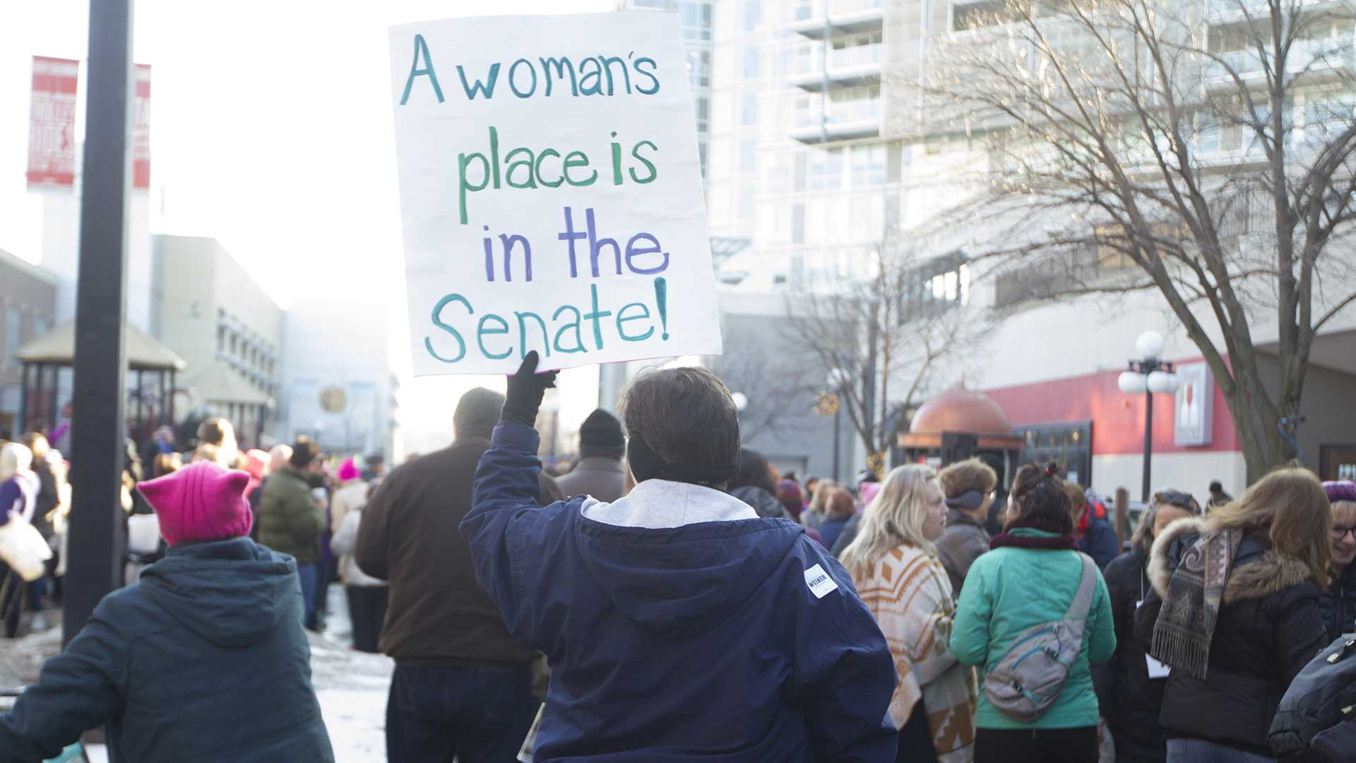 A demonstrator holds her sign during the Women's March on January 20, 2018. Hundreds gathered on the Ped Mall to listen to speakers and march for women's rights. (Katie Goodale/The Daily Iowan)