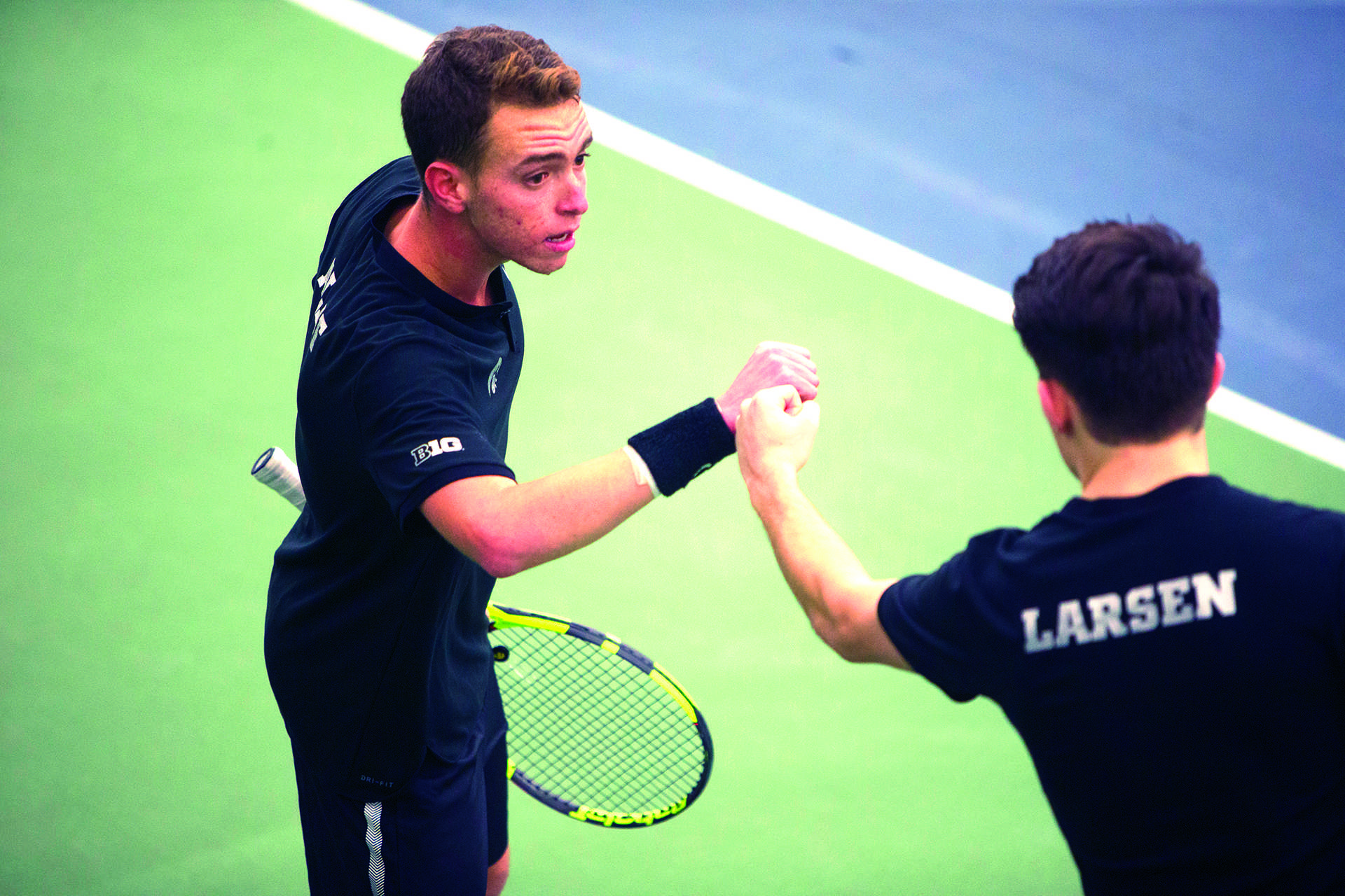 Iowa's Jonas Larsen and Kareem Allaf bump fists during a tennis match between Iowa and Western Michigan in Iowa City on Friday, Jan. 19, 2018. The Hawkeyes earned the doubles point but lost the match overall, 5-2. (Shivansh Ahuja/The Daily Iowan)
