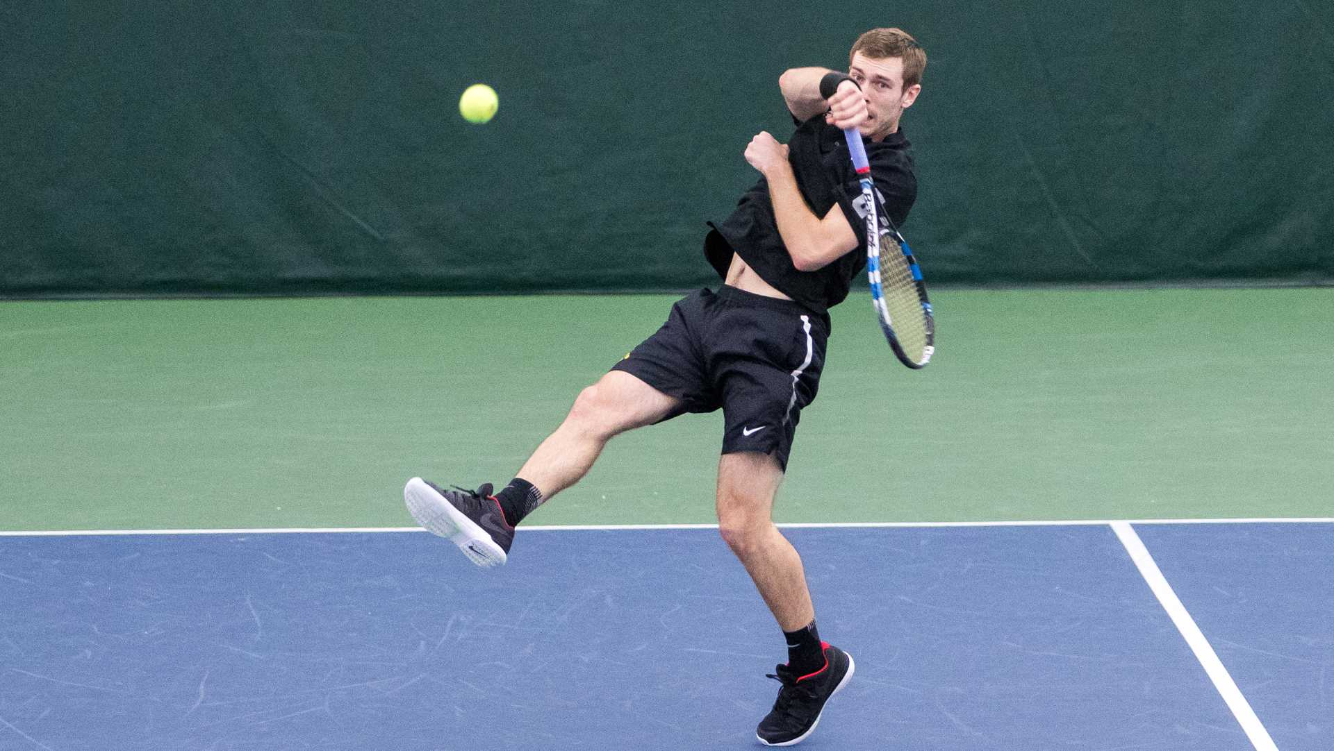 Iowa tennis player Jake Jacoby volleys the ball during a doubles match against Cornell University on Friday, Mar. 2, 2017. Jacoby lost his match 5-7 and the Big Red defeated the Hawkeyes 4-3. (David Harmantas/The Daily Iowan)