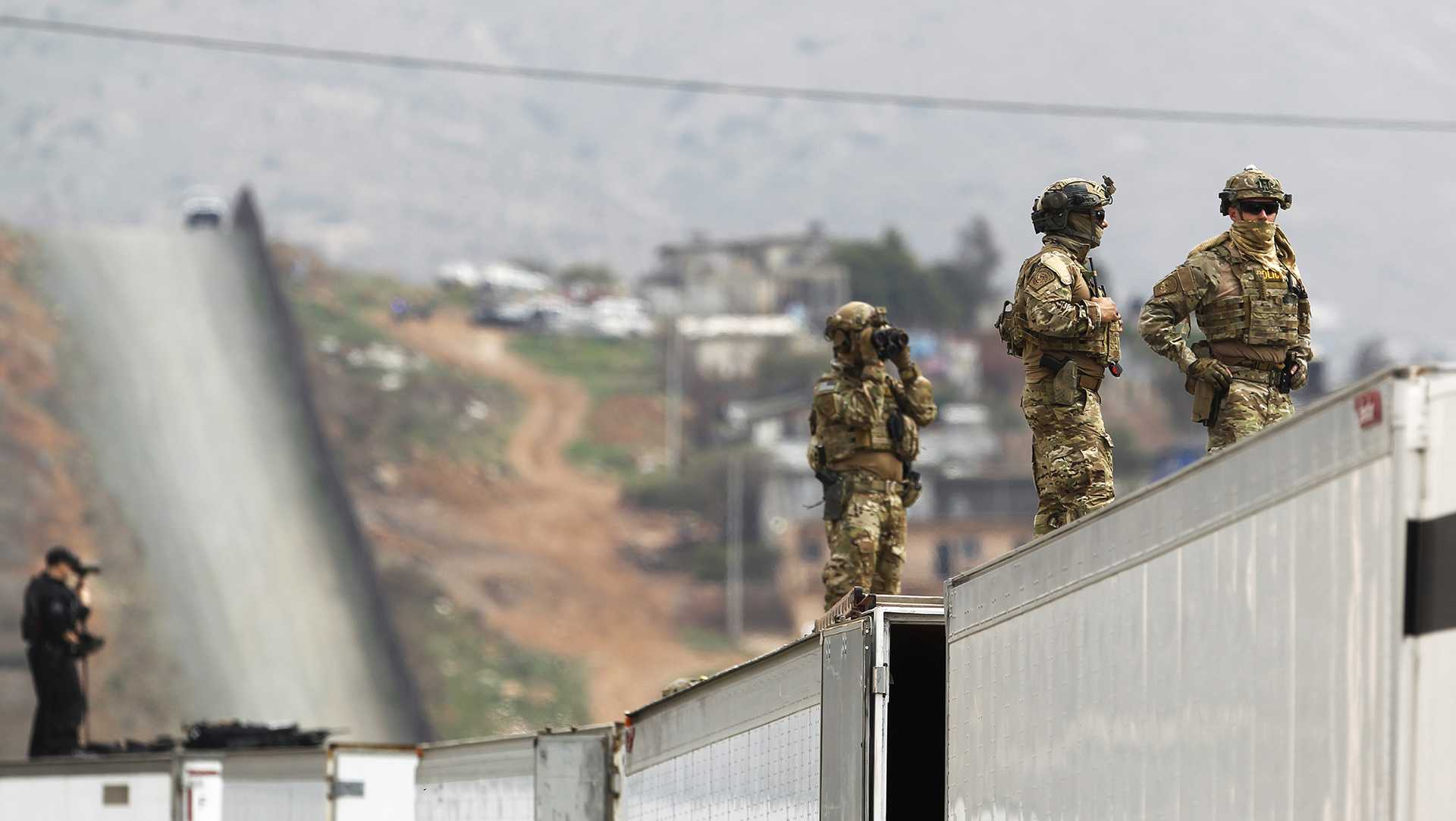 Military Police keep watch near the Mexico border as President Donald Trump takes a tour of the border wall prototypes near the Otay Mesa Port of Entry in San Diego County, Calif., on March 13, 2018. (K.C. Alfred/San Diego Union-Tribune/TNS)