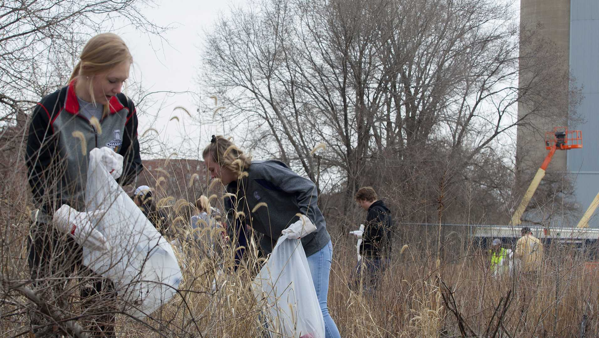 From left: Freshman Emma Rotz and Freshman Abby Thornton pick up trash by the Iowa River during IIHR's river clean up on Saturday Apr. 21, 2018. THe IIHR hosted an Earth Day event during which community members were invited to come pick up trash along the Iowa River. (Katie Goodale/The Daily Iowan)