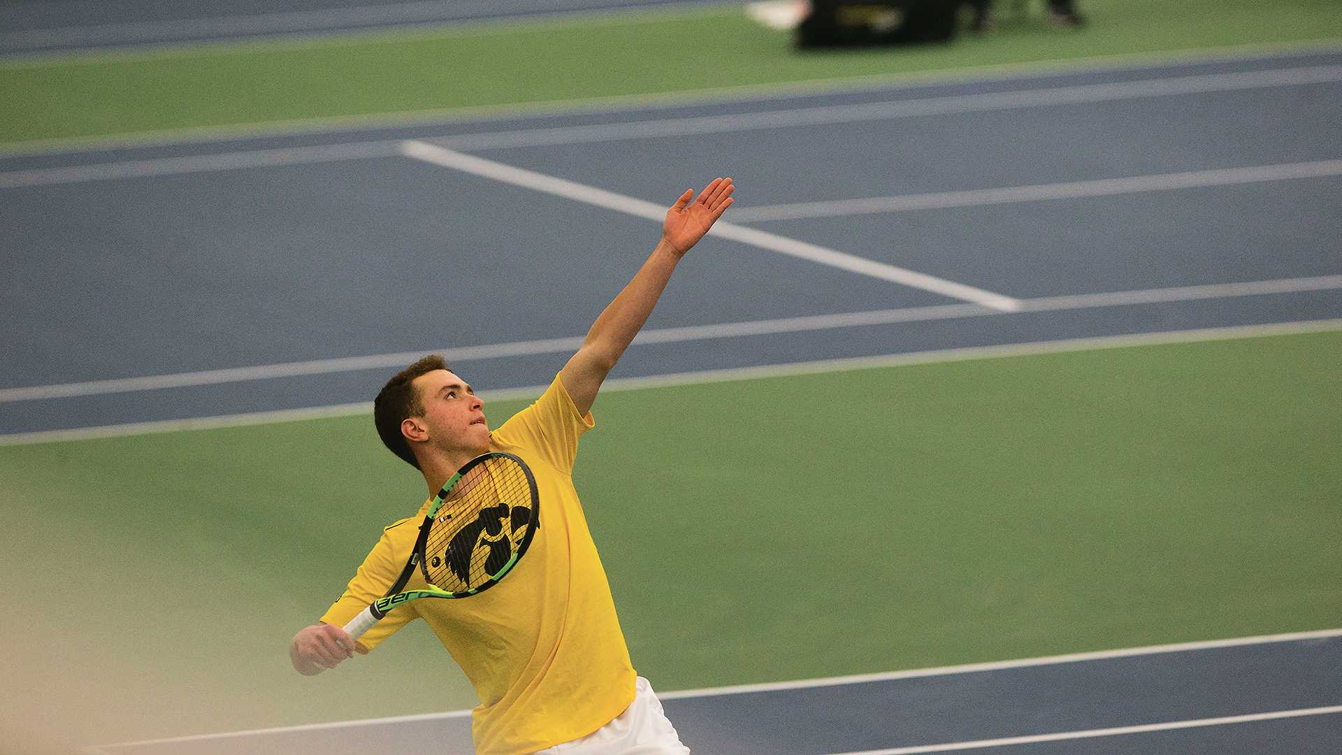 Iowa's Piotr Smietana serves a ball during the Iowa/Creighton tennis match at the Hawkeye Tennis and Recreation Complex on Friday, Feb. 16, 2018. The Hawkeyes defeated the Bluejays, 7-0. (Lily Smith/The Daily Iowan)