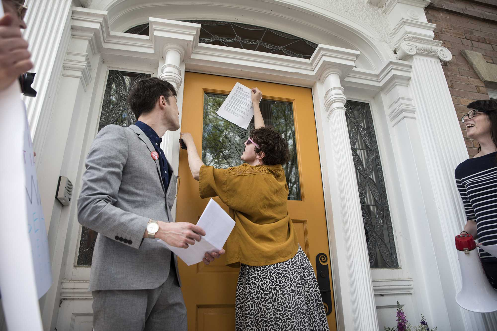 Meaghan Harding tapes a letter to the door of Bruce Harreld's home on May 4, 2018. UI's non-tenured faculty—grown to 52% since 2011—advocated for greater job security, fair pay, and benefits. (The Daily Iowan/Olivia Sun)