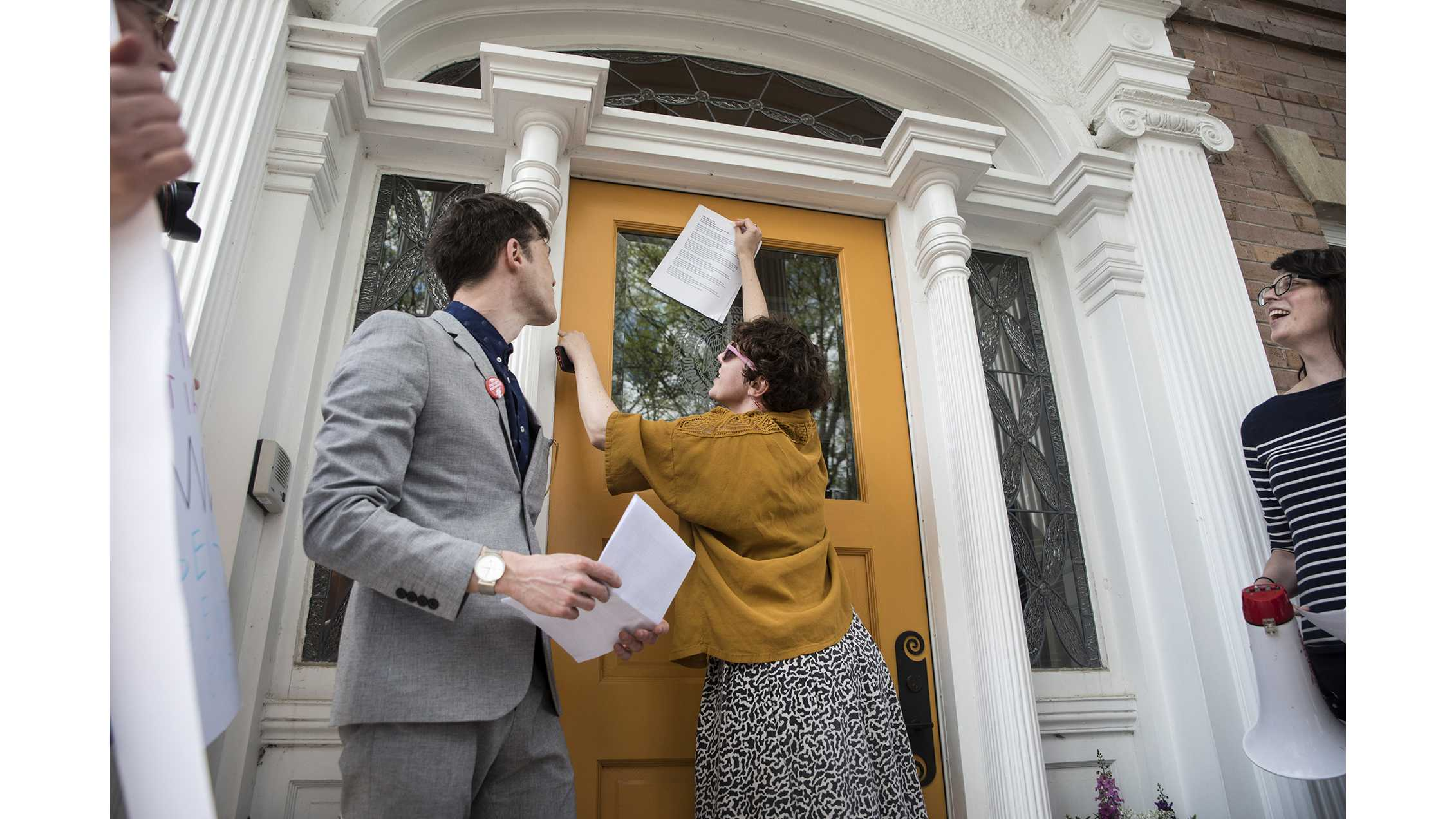 Meaghan Harding tapes a letter to the door of Bruce Harreld's home on May 4, 2018. UI's non-tenured faculty—grown to 52% since 2011—advocated for greater job security, fair pay, and benefits. (Olivia Sun/The Daily Iowan)