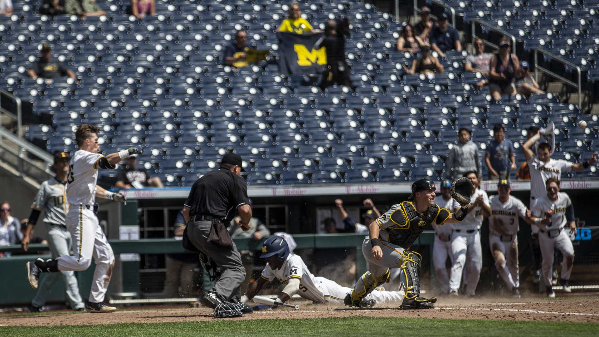 Michigan's Christian Bullock slides into home on a sac fly in to win the game during Iowa's Big Ten tournament Game against Michigan at TD Ameritrade Park in Omaha, Neb. on Wed. May 23, 2018. The Wolverines defeated the Hawkeyes 2-1 in extra innings. (Nick Rohlman/The Daily Iowan)