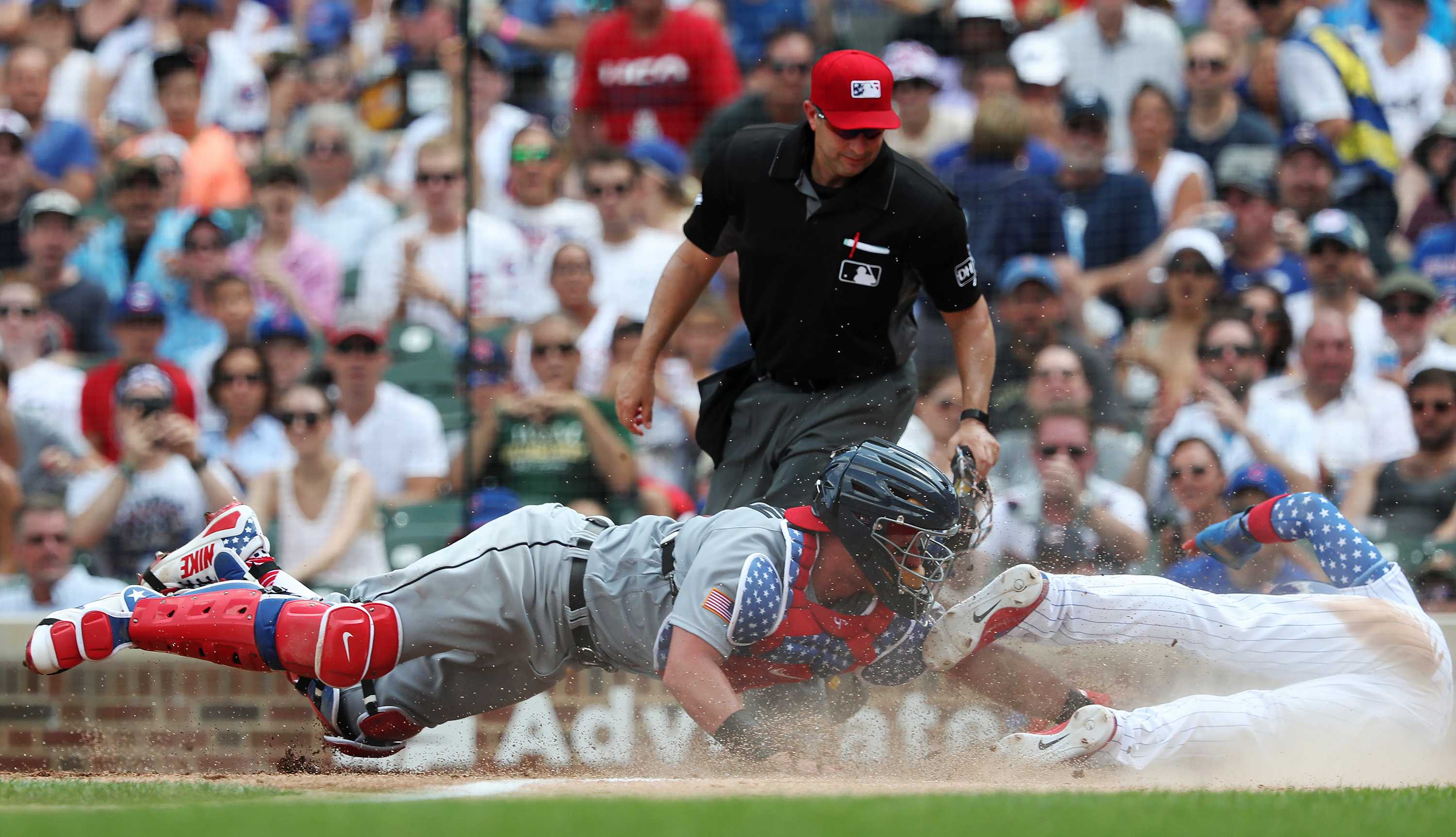 Chicago Cubs second baseman Javier Baez (9), right, steals home plate for a run as Detroit Tigers catcher James McCann (34) reaches for the late tag in the fourth inning at Wrigley Field Wednesday, July 4, 2018, in Chicago. (John J. Kim/Chicago Tribune/TNS)