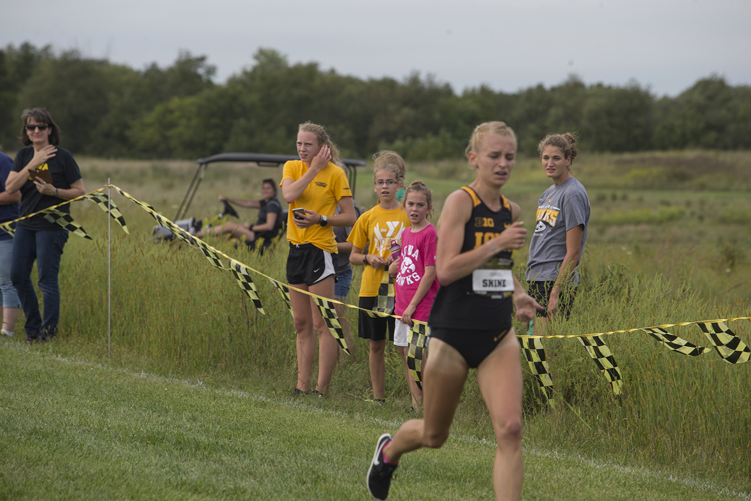 Bystanders look on as Senior Andrea Shine runs through the finish line during the Hawkeye Invitational at Ashton Cross Country course on Friday, August 31, 2018. Iowa State won the meet with a score of 24, while the Hawkeyes finished second with a score of 56. Shine placed first in the Women's 4K with a time of 14:07.5.