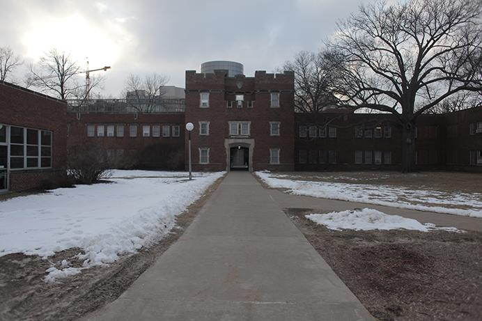 Construction cranes overlook Quadrangle Hall on Tuesday, Feb. 17, 2015. Quad was built in 1920 and was used as a barracks during World War I before housing students. (The Daily Iowan/Mikaela Parrick)