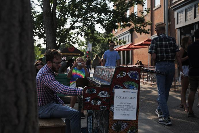 Chase Garrett performs on the Washington Street piano on Wednesday. The piano is one of several downtown and near downtown that give members of the community an opportunity to play. (The Daily Iowan/Jordan Gale)