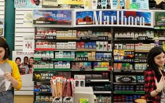 Rows of cigarettes line the wall behind the counter at The Den in Iowa City on Wednesday, Aug 26, 2015.