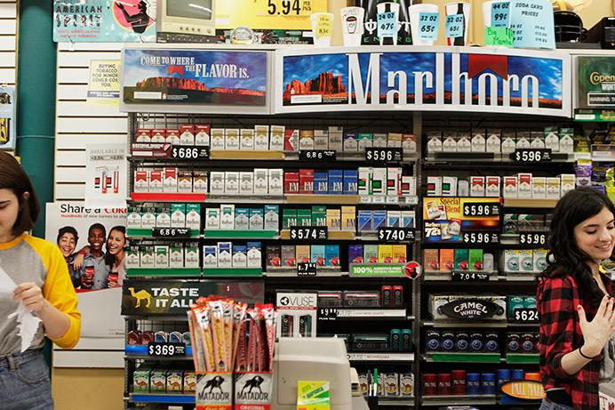 Rows of cigarettes line the wall behind the counter at The Den in Iowa City on Wednesday, Aug 26, 2015. The UI recently adjusted the campus-wide smoking ban to include all tobacco products and electronic cigarettes. (The Daily Iowan/Lexi Brunk)