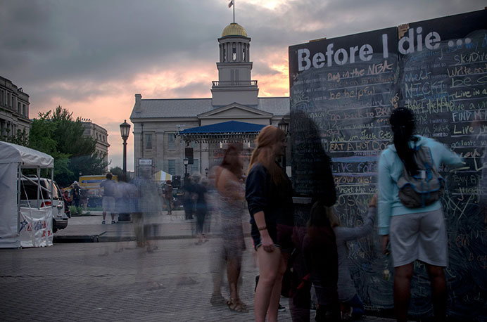 "Community members write on the ""Before I Die"" wall while at the Iowa City Soulfest on Saturday, Aug. 29, 2015. (The Daily Iowan/Jordan Gale)"