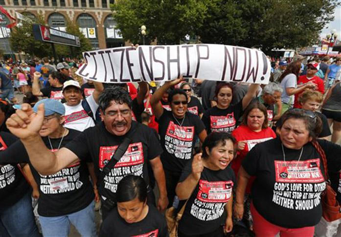 Immigrant rights protesters rally as Republican presidential candidate, Louisiana Gov. Bobby Jindal speaks at the Iowa State Fair Saturday, Aug. 22, 2015, in Des Moines, Iowa. (AP Photo/Paul Sancya)