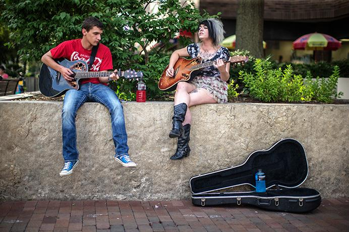 Caleb Wachendorf and Alyssa Kaley Charmen play music on the Pedestrian Mall on Wednesday. Charmen is originally from Buffalo, New York. (The Daily Iowan/Sergio Flores)