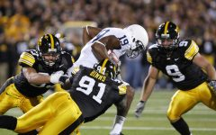 David Scrivner/The Daily Iowan Iowa's Broderick Binns takes down Penn State's Justin Brown during their game on Saturday, Oct. 2, 2010 in Kinnick Stadium.