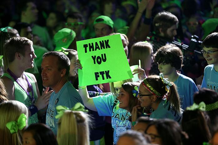 FILE - A Dance Marathon family member carries an FTK sign during the first hour of the Big Event in the IMU on Feb. 6, 2015. This is Dance Marathons 21st Big Event at UI. (The Daily Iowan/file)