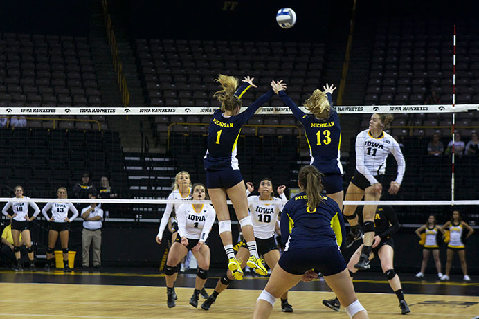 Iowa+outside+hitter+Reagan+Davey+hits+the+ball+against+Michigan%E2%80%99s+Claire+Kieffer-Wright+and+Katherine+Mahlke+in+Carver-Hawkeye+on+Wednesday.+Michigan+beat+Iowa%2C+3-2.+%28The+Daily+Iowan%2FCourtney+Hawkins%29