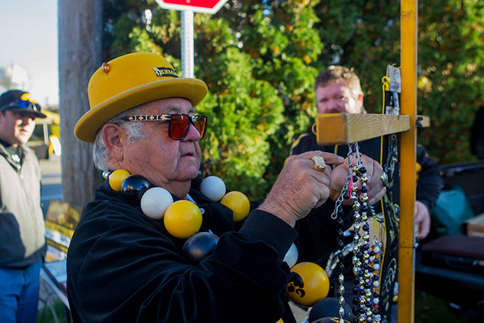 The Hawkeye Ambassador hangs his beads on a cross near Melrose Ave. on Saturday, Oct. 10, 2015. Ryan has been selling souvenirs for about 30 years. (The Daily Iowan/Peter Kim)